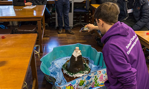 A secondary school student conducting a model volcano experiment at the University
