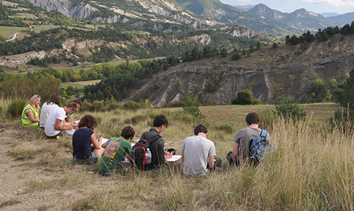 A group of students looking out and taking notes while on a field trip