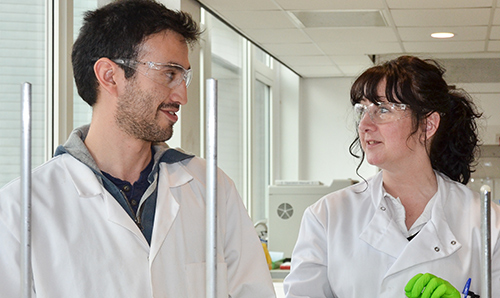 A man and woman in lab coats, in discussion.