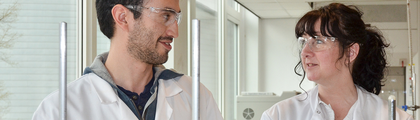 A man and woman in lab coats and in discussion