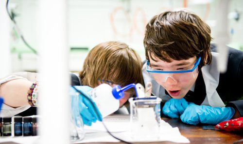 Two primary school children excitedly watching an experiment