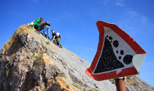Students climbing a rock against a blue sky on field trip