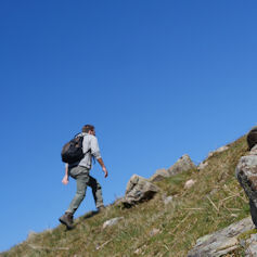 Man with rucksack walking up a hillside against a blue sky