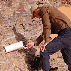 Man using equipment to take a reading from rockface