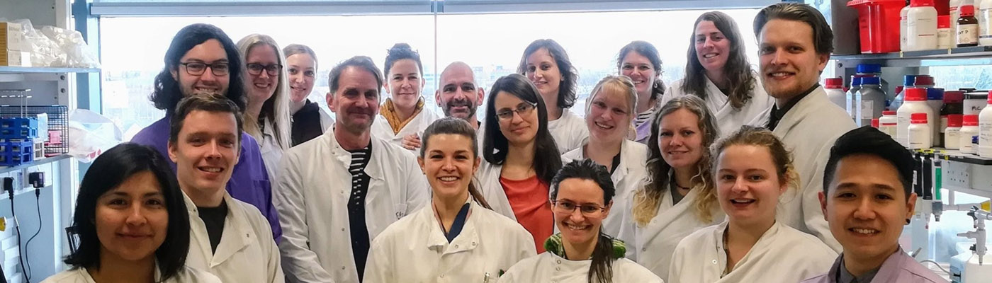 A group of scientists in white lab coats stand in a lab and smile for a group photo.