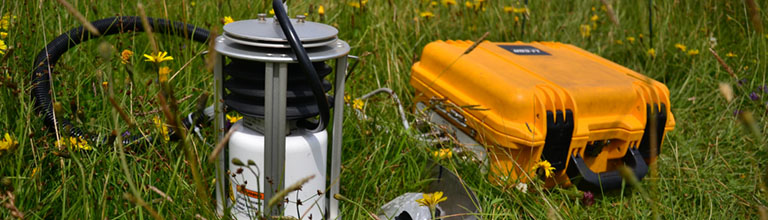 Scientific equipment and a yellow box lay among long grass in a meadow.