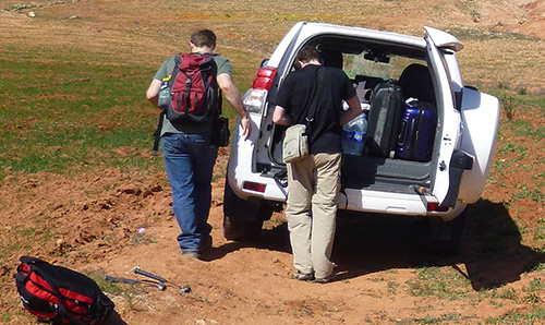 Two researchers taking kit out of their van in a field in Morocco