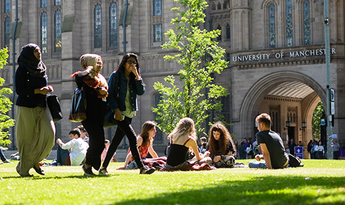 Students sat on the grass on camous during an open day