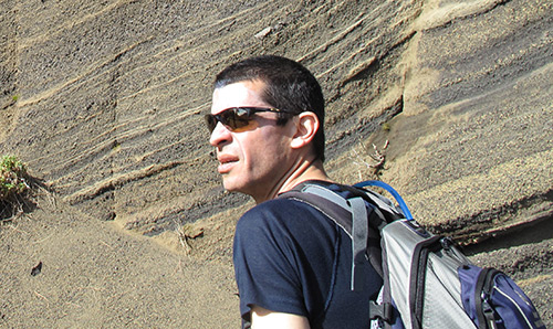 A man in sunglasses peering out in front of a cliff face