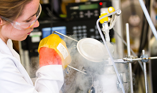 A female researcher pouring out a steam-filled container