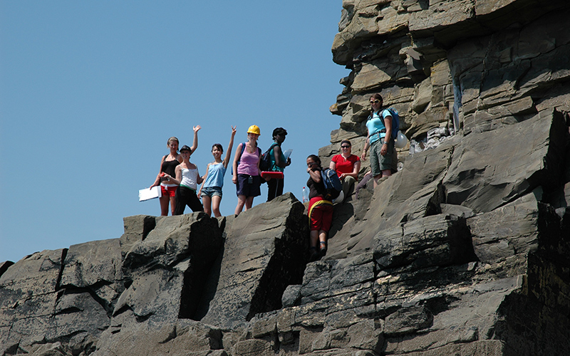 Students waving from a rock face in Pembroke