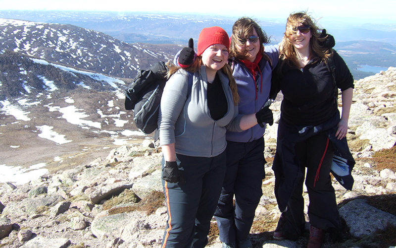 Three female students smiling atop a mountain in Scotland