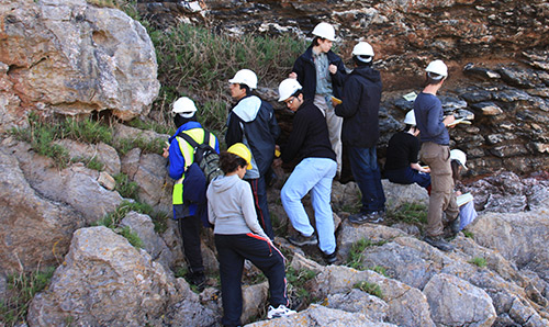 Students in hard hats examining a cliff face