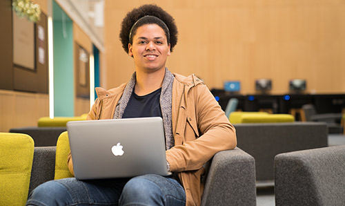A male student smiles at the camera from behind his laptop