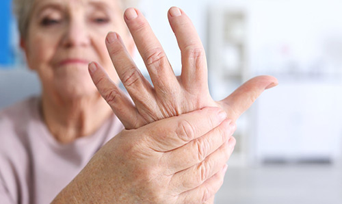 An elderly woman holding her hand in pain